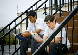 Students reading books on stairs